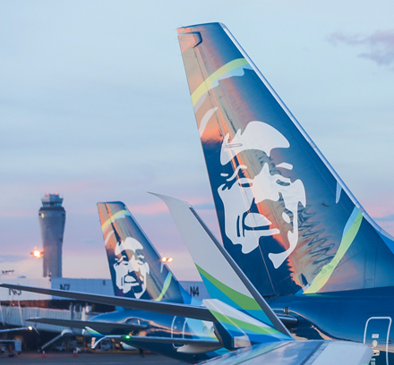 Two airplanes at sunset in Seattle at the airport.